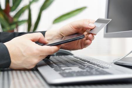 남자를위한 신용 카드 및 휴대 전화를 사용하는 선 지불 모바일 쇼핑 개념