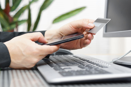 Man is using credit card and mobile phone for  on line payment  mobile  shopping concept photo