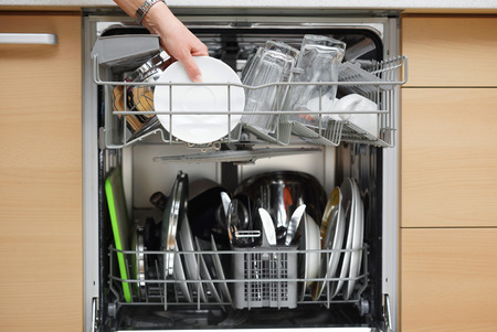 dirty room: woman is using a dishwasher in a modern kitchen