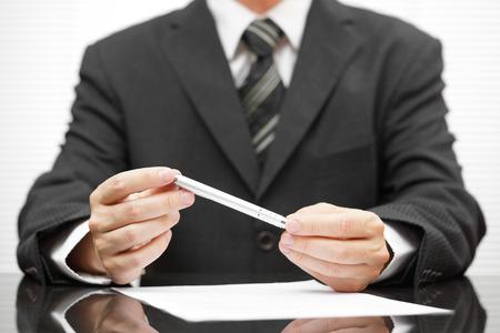 zakenman die pen over voorgestelde contract en denken over de deal te maken