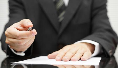 firmando: De negocios que ofrece una pluma para firmar un contrato Foto de archivo