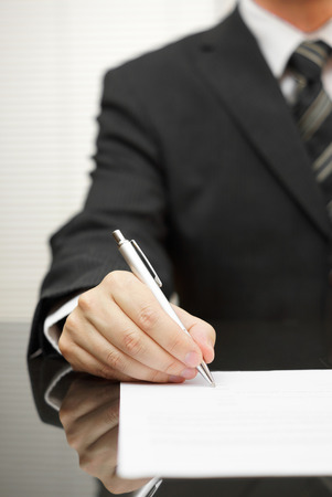 fulfill: businessman is signing document Stock Photo