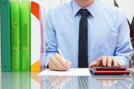 businessman with full of paperwork is completing form photo