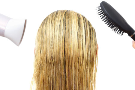 Woman using hairdryer  and  comb photo