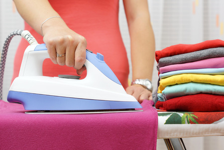iron curtain: Ironing Clothes On Ironing Board Stock Photo