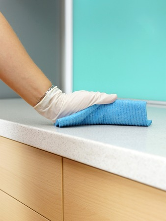 Woman Wearing Apron Cleaning Kitchen worktop photo