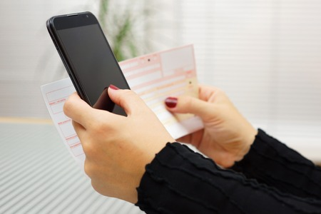 e banking: Woman is paying bill on mobile smart phone Stock Photo