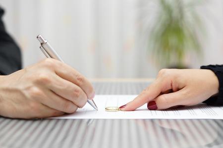 ringe: Mann Unterzeichnung Scheidungsvereinbarung und Frau wegschieben Jäten Ring