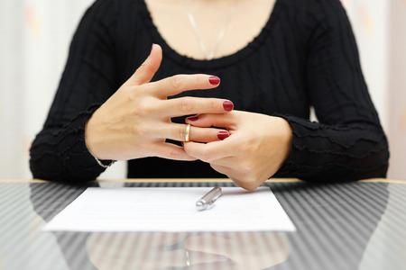 divorcio: romper mujer est� tomando el anillo de la mano Foto de archivo