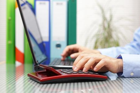 Geschäftsmann mit voller Mappen und Ordner auf Laptop und Rechner arbeiten