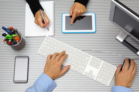 Businessman in businesswoman working together in office  Using tablet pc and computer  Top view photo