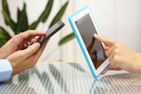 woman and man transferring application from smart mobile phone to tablet pc photo