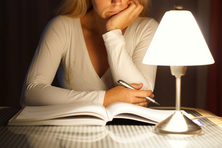 under pressure: female student is reading book late at night Stock Photo