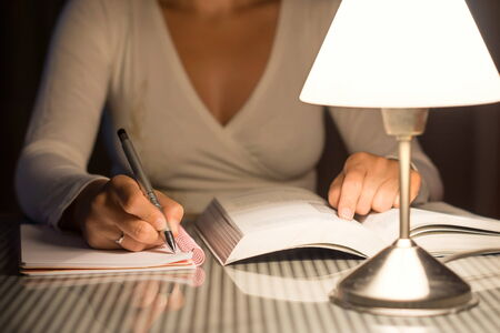 night school: woman is studying and take notes late at night