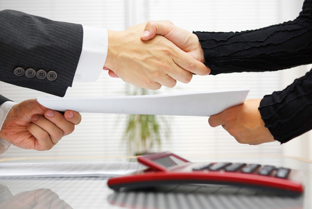 insurance consultant: businesswoman and businessman are handshaking and exchanging contract documents Stock Photo