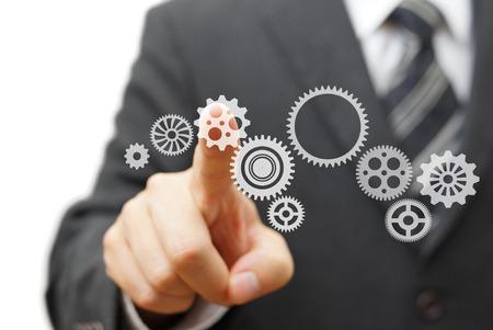 growth: El hombre de negocios est� en contacto con la rueda dentada virtual. Tecnolog�a y Visi�n Foto de archivo