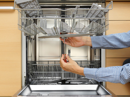 handyman repairing a dishwasher Stock Photo