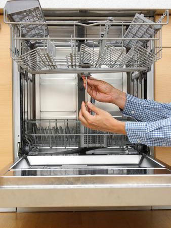 handyman repairing a dishwasher Stock Photo