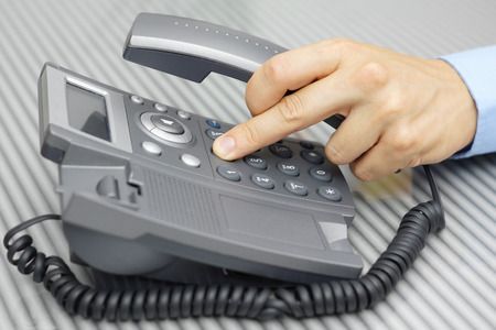 Business man hand is dialing a phone number with picked up headset photo