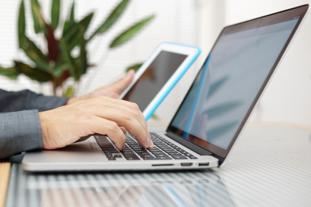 Man using laptop and tablet pc at the same time photo