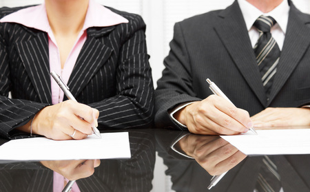 businesswoman and businessman signing contract after negotiations photo