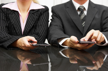 businessman and businesswoman using smart phone on meeting photo