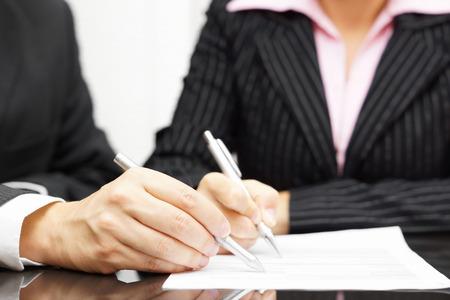 Vrouw en man zijn het analyseren en het vervullen van document