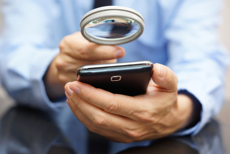 Businessman using mobile smart phone with magnifying glass . Phone fraud concept photo