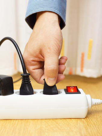 human energy: man unplugged plug from the power board Stock Photo