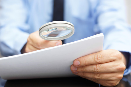 Businessman looking through a magnifying glass to contract photo