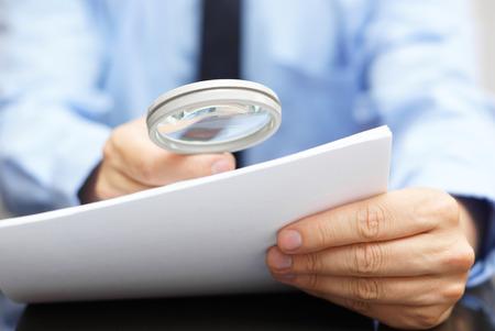Podnikatel se dívali přes zvětšovací sklo na smlouvu Reklamní fotografie