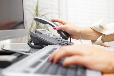 Frau hebt das Headset vom Telefon, Hilfekonzept