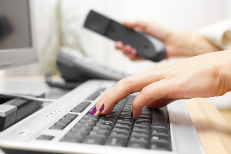 contacts: Businesswoman is typing on keyboard and answer the call. customer service concept Stock Photo