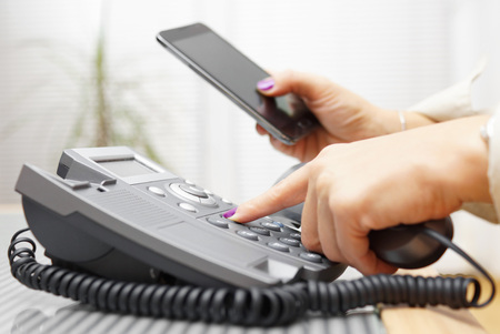 contact centre: Woman is dialing on land line phone and looking on mobile phone