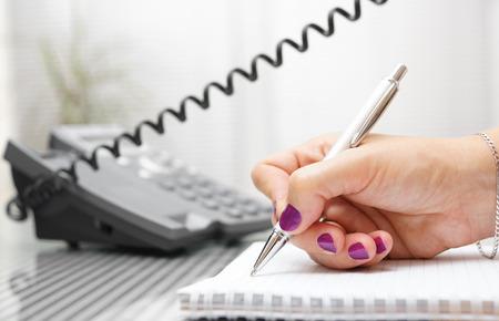 landline: Imprenditrice sta parlando al telefono e prendere appunti