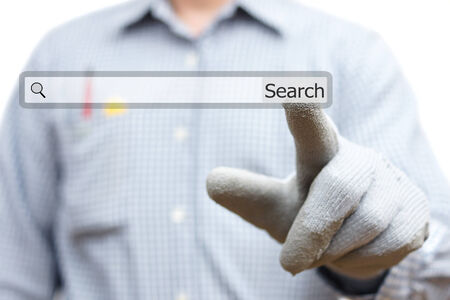 Construction worker pointing with finger on search bar photo