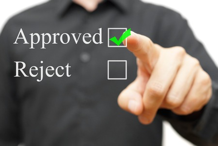 Young businessman pressing  mark approved photo