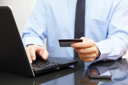 De zakenman is met behulp van een creditcard voor on line betaling op de laptop