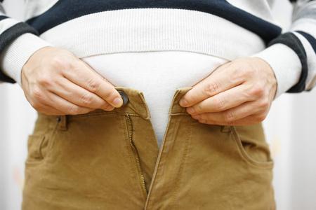 ombligo: el hombre es incapaz de cerrar sus pantalones debido a aumentar de peso Foto de archivo