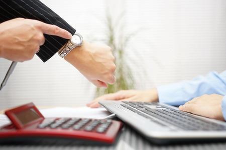 empleados trabajando: jefe est� apuntando al reloj, es tarde con el trabajo, la presi�n sobre el lugar de trabajo