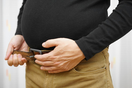 weight gain: men can not sing belt on his pants due to big stomach Stock Photo