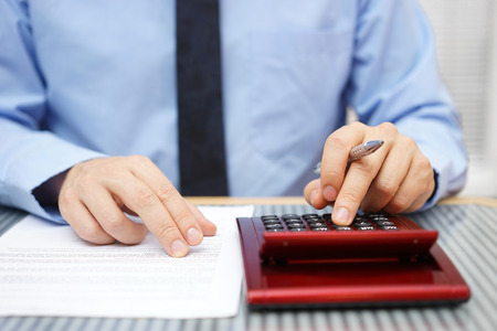 small paper: Businessman calculating  and checking articles of agreement