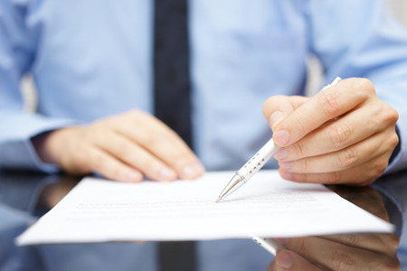 audit: businessman in office is analyzing document Stock Photo