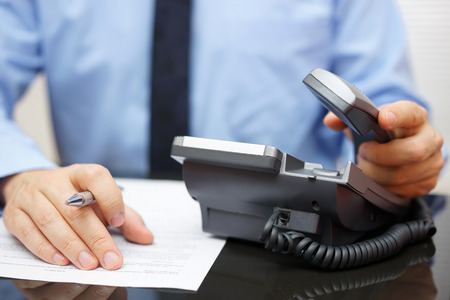 Businessman is picking up the headset for help, while reading legal document