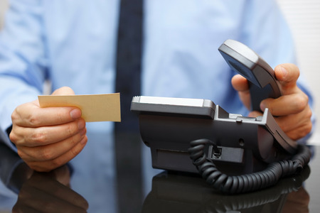 phone conversations: businessman holding business card and calling his client Stock Photo