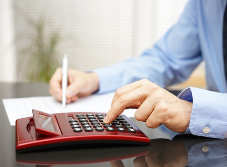 bank rate: Businessman working in  office with calculator and fulfilling documernt Stock Photo