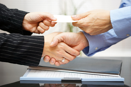 Business clients are exchanging business card  and handshakeing after successful meeting Stock Photo