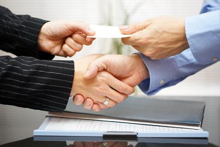 Geschäftskunden austauschen Visitenkarte und handshakeing nach erfolgreicher Tagung