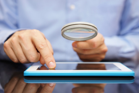 magnifying glass man: Businessman using tablet computer  with magnifying glass . Caution in the use of tablet or buying application