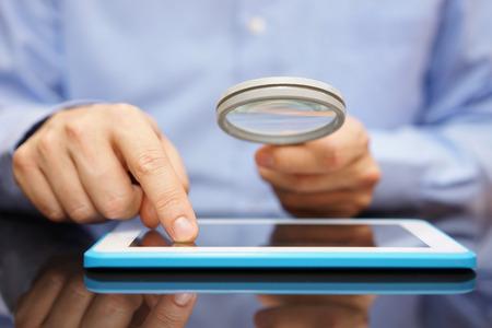 Zakenman met behulp van tablet-computer met vergrootglas. Voorzichtigheid is geboden bij het gebruik van de tablet of het kopen applicatie